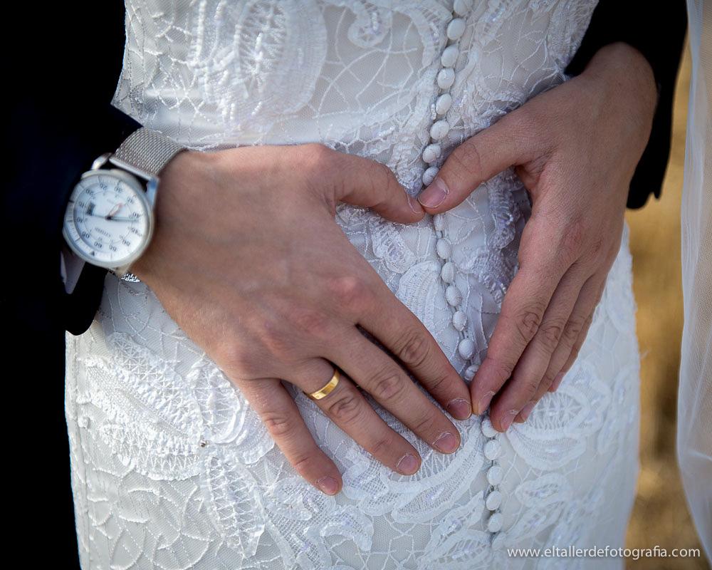 Detalle de las manos del novio sobre el vestido de la novia durante el reportaje de posboda