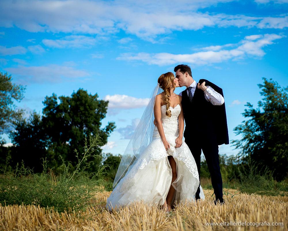 Pareja de novios besándose durante la posboda en un campo cerca de Aranjuez al atardecer