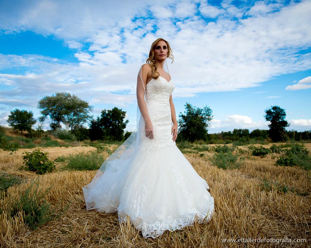 Novia con un cielo azul y trigo recién segado en los campos de Aranjuez
