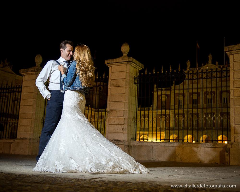 Fotografía de una novia con una cazadora vaquera tirando de los tirantes del novio por la noche en el Palacio Real de Aranjuez