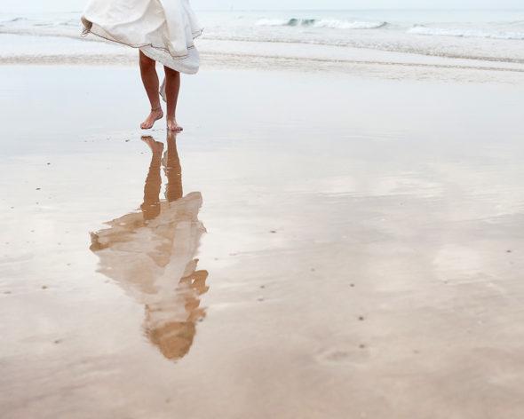 Niña de comunion descalza andando por la orilla de la playa y reflejada en el agua