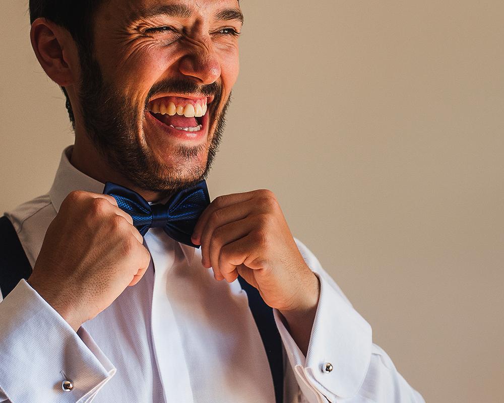 Detalle de la sonrisa del novio mientras se ajusta la pajarita