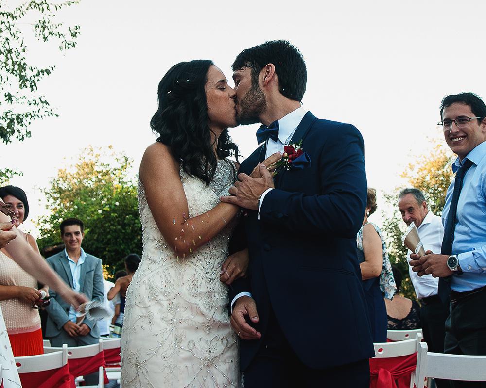 Beso de los novios a la salida de la ceremonia durante el arroz