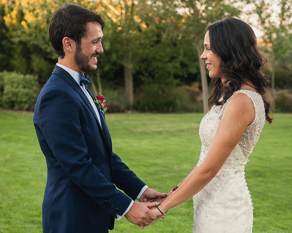 Fotos de novios frente a frente cogidos de la mano durante el reportaje de recién casados