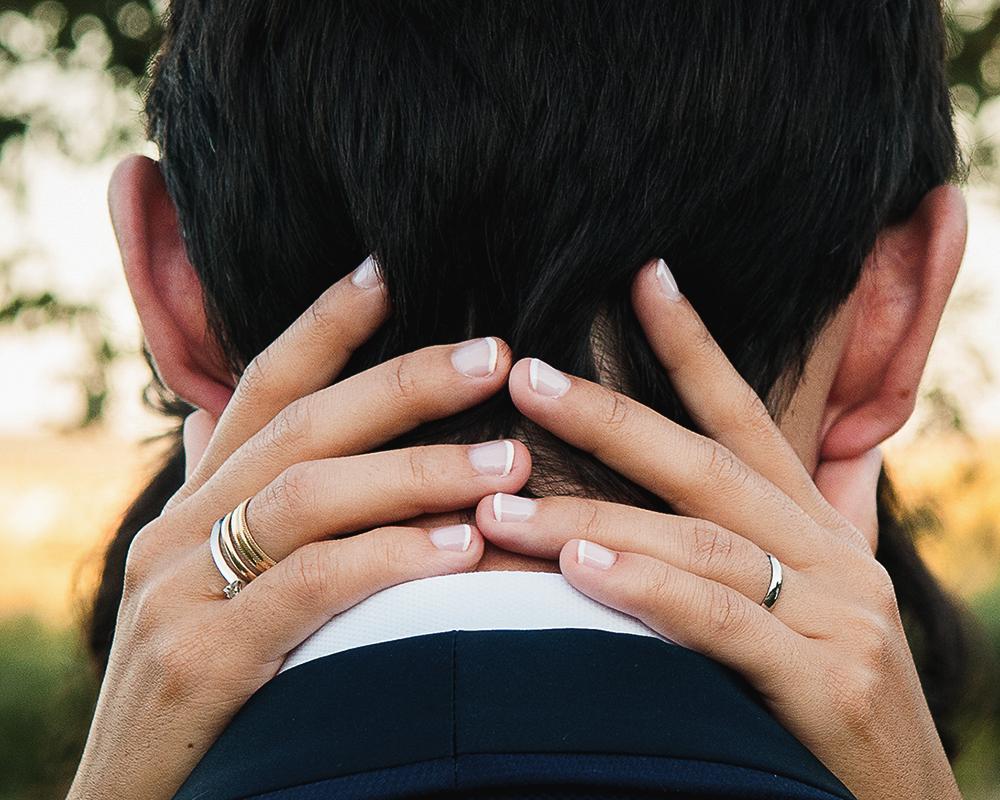 Manos de la novia en el cuello del novio con la alianza y el anillo de pedida