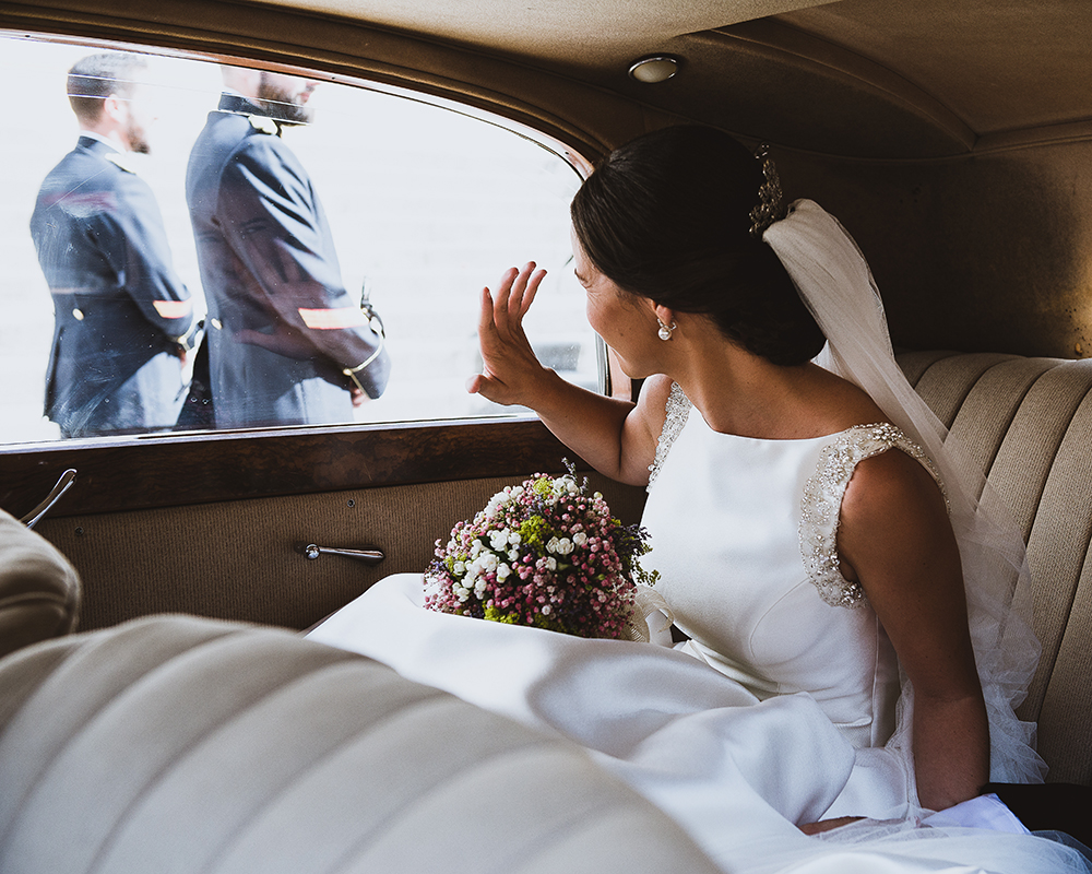 Novia saludando desde el coche a la llegada a la ceremonia