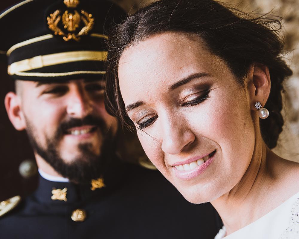 Retrato de una novia sonriente con el novio detras un poco desenfocado vestido de militar