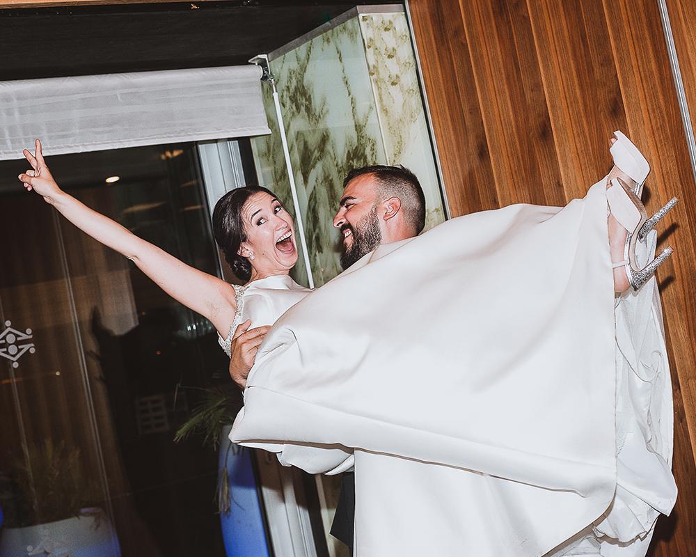 Novia en Brazos del novio hace el signo de victoria durante la celebración en el Parador de Cádiz