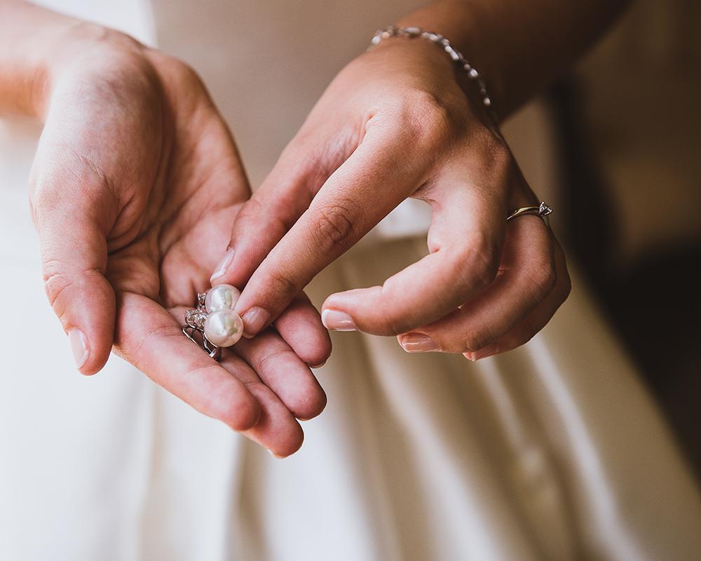 Manos de la novia con sus pendientes mientras se prepara para salir de casa hacia la iglesia