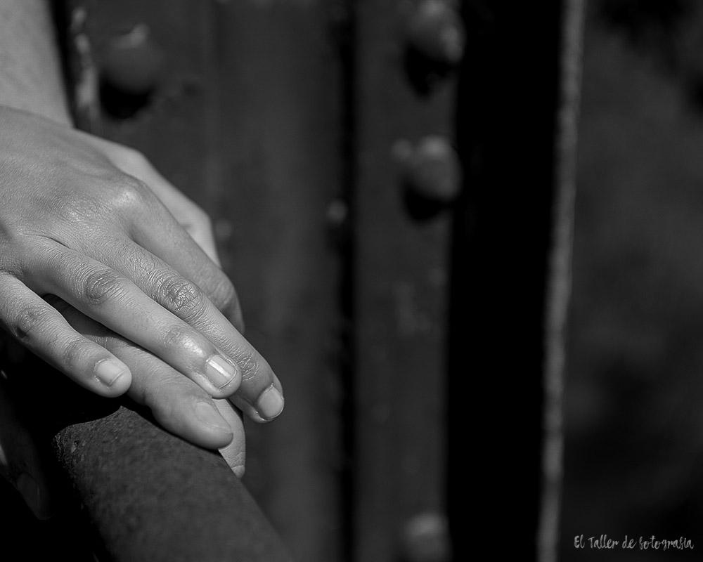 Detalle de unas manos sobre la pasarela de un puente de hierro abandonado