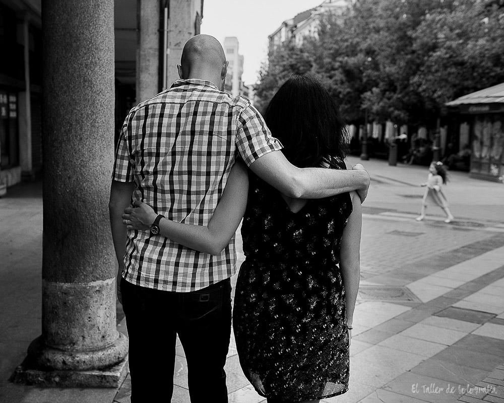 Pareja de novios de espaldas muy unidos paseando por la calle