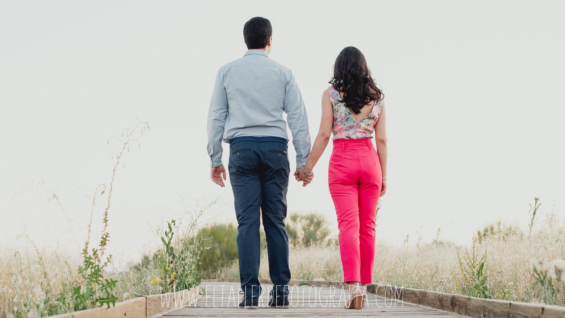 Los novios caminando por una pasarela de espaldas