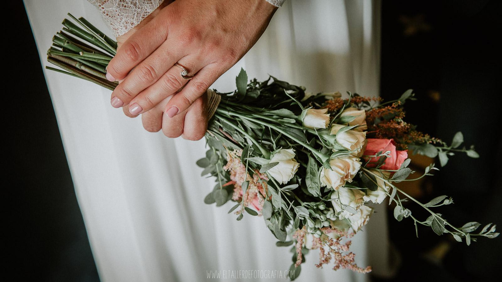 Detalle del anillo de pedida junto con el ramo de la novia